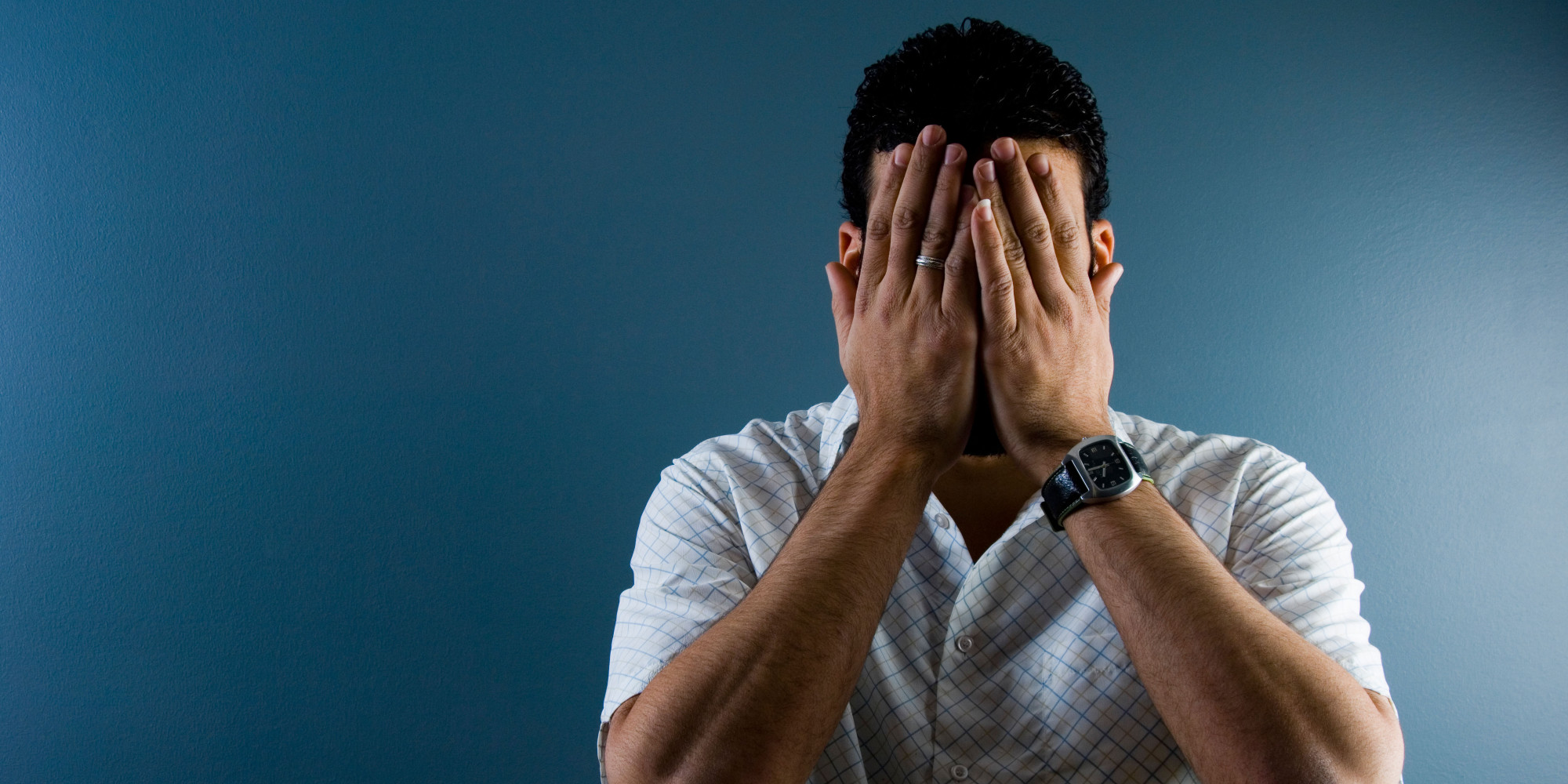 A3DATJ Contemporary image of a man hiding his face indoors